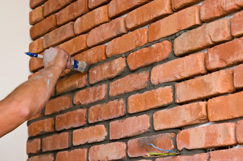 Process of making a red brick wall, home renovation. Home renovation or remodelling: process of making red brick wall using old vintage bricks fronts Whole stock image