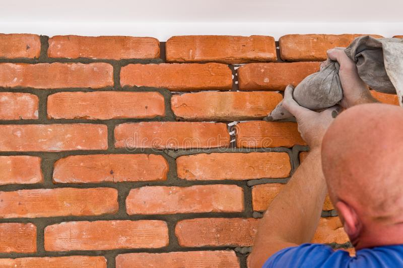 Process of making a red brick wall, home renovation. Home renovation or remodelling: process of making red brick wall using old vintage bricks fronts Whole royalty free stock photo