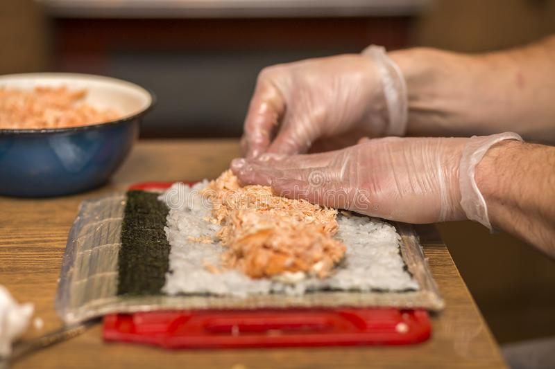 Process of making sushi and rolls. Close-up of man chef hands preparing traditional Japanese food at home or in restaurant on. Kitchen table royalty free stock photo