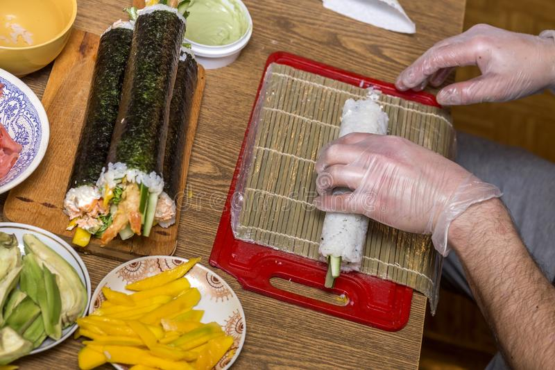 Process of making sushi and rolls. Close-up of man chef hands preparing traditional Japanese food at home or in restaurant on. Kitchen table royalty free stock photos