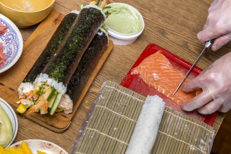 Process of making sushi and rolls. Close-up of man chef hands preparing traditional Japanese food at home or in restaurant on. Kitchen table royalty free stock photography