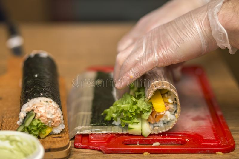 Process of making sushi and rolls. Close-up of man chef hands preparing traditional Japanese food at home or in restaurant on. Kitchen table stock photos