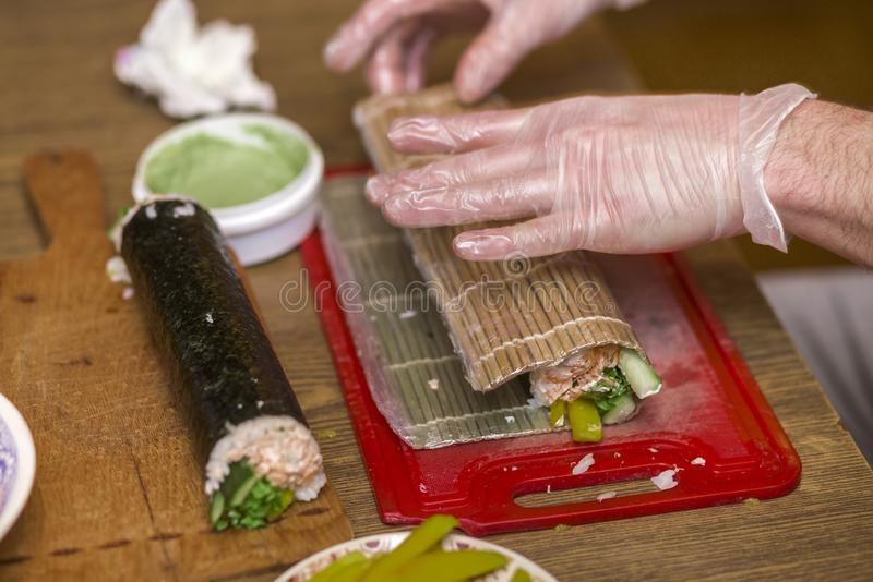 Process of making sushi and rolls. Close-up of man chef hands preparing traditional Japanese food at home or in restaurant on. Kitchen table stock images