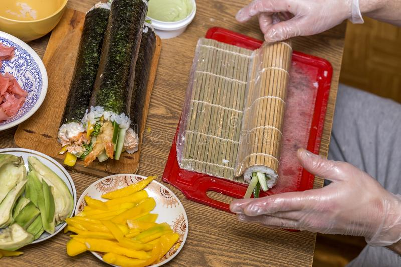Process of making sushi and rolls. Close-up of man chef hands preparing traditional Japanese food at home or in restaurant on. Kitchen table stock photo