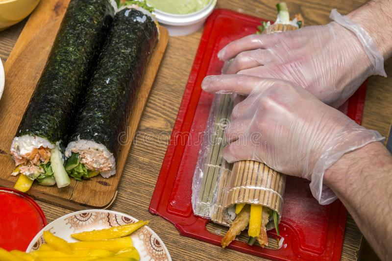 Process of making sushi and rolls. Close-up of man chef hands preparing traditional Japanese food at home or in restaurant on. Kitchen table royalty free stock image