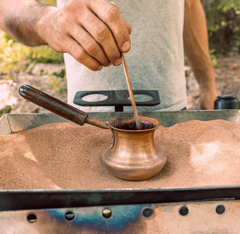 The process of making Turkish coffee on hot sand in a Turk. With male hands, barista. The process of preparing traditional Turkish coffee on hot sand in a Turk stock photos