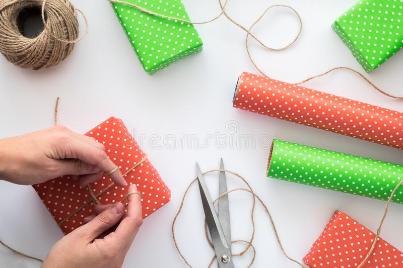 Process of package and wrapping Christmas and New Year gift box with woman hands. Wrapping paper, scissors, twine on the white bac royalty free stock photography