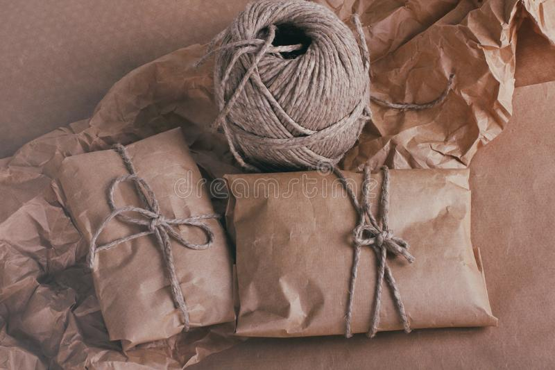 Process of packaging parcels. Pouch wrapped in brown craft paper and tie hemp cord. Crumpled paper texture background. stock photos