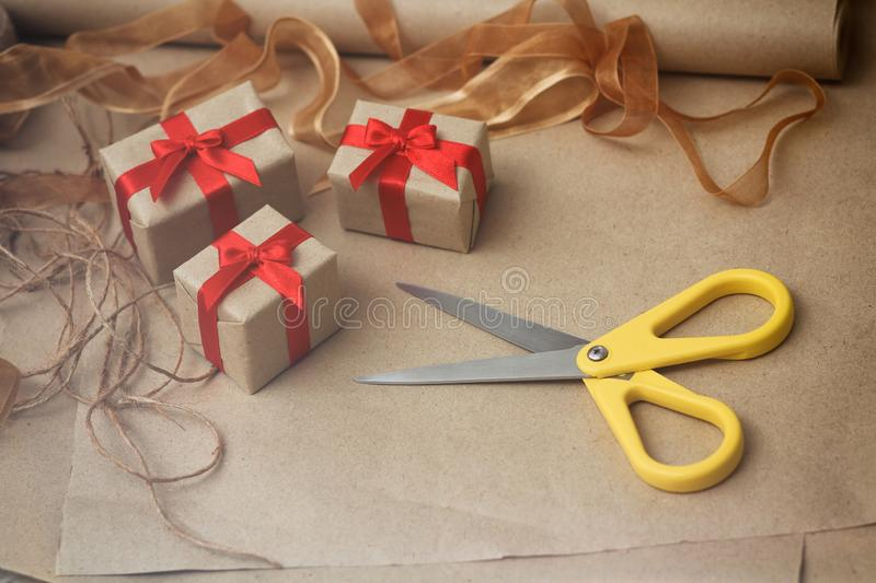 Process of packing presents in gift boxes. Craft paper, scissors, hemp threads, red satin ribbon. Gift wrapping. Process of packing presents in gift boxes stock photography