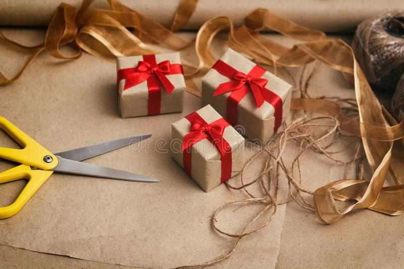 Process of packing presents in gift boxes. Craft paper, scissors, hemp threads, red satin ribbon. Gift wrapping. Process of packing presents in gift boxes stock photos