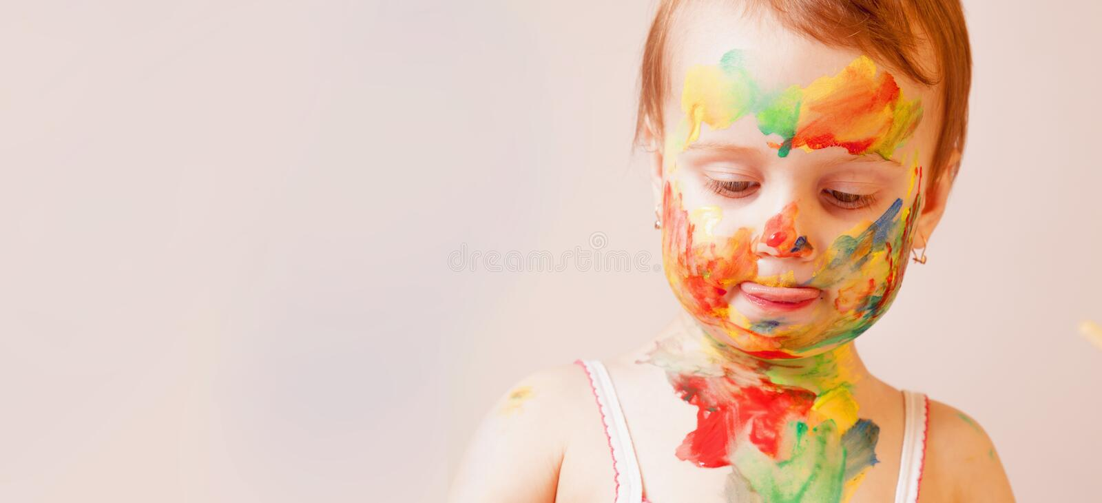 Process of painting. Little cute girl with children`s colorful makeup showing painted hands. Art concept.  royalty free stock image