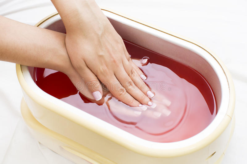 Process paraffin treatment of female hands. In beauty salon royalty free stock photo