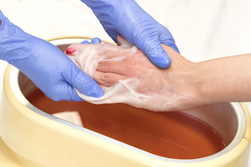 Process paraffin treatment of female hands. In beauty salon royalty free stock photos