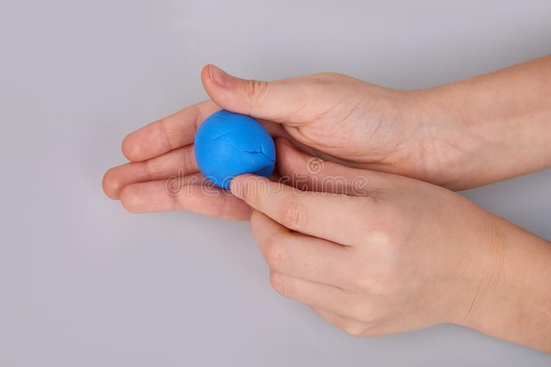 The process of play dough modeling, the child`s hands sculpt figures. Play dough in preschool or nursery for education concept. Piece of blue plasticine in the royalty free stock photo