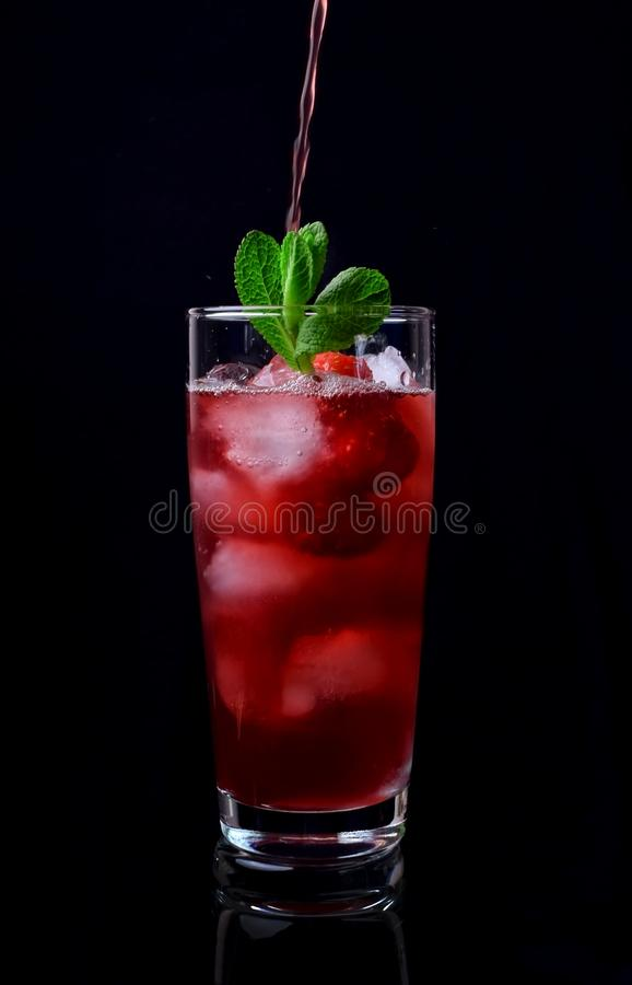 Process of pouring the red drink into a tall glass filled with ice cubes, raspberries and mint stock image