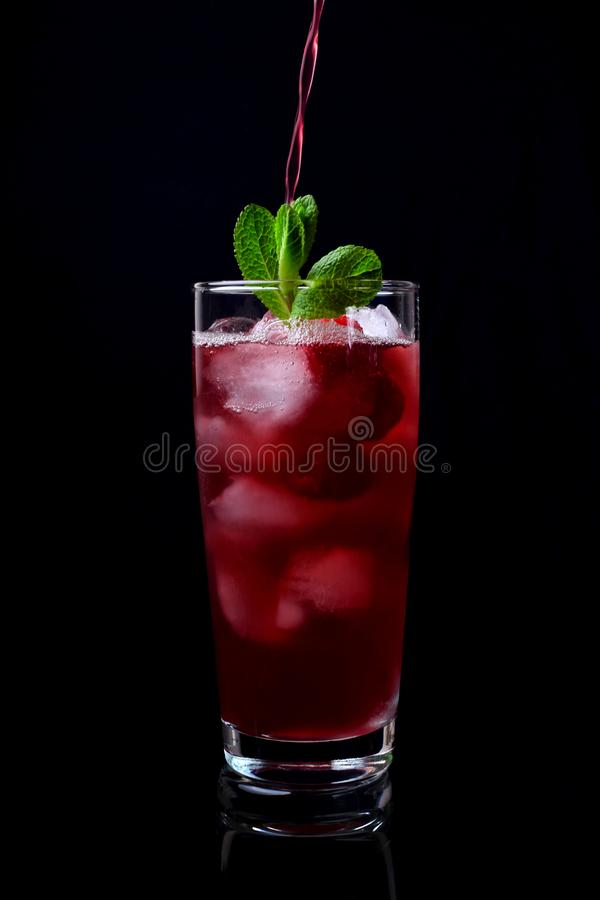 Process of pouring the red drink into a tall glass filled with ice cubes, raspberries and mint stock photography