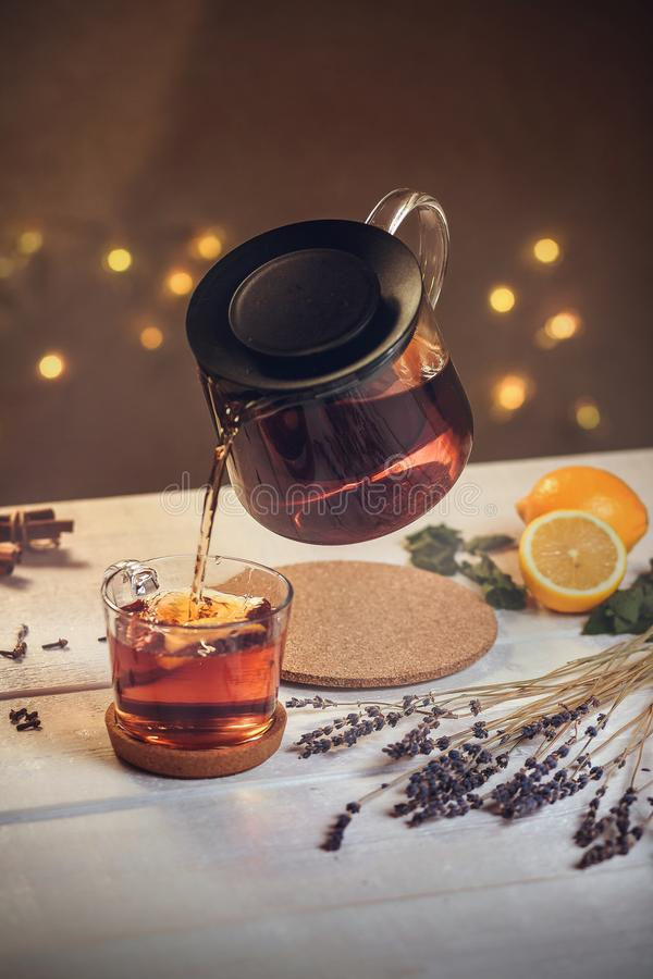 The process of pouring tea into a mug of teapot. Levitation, on a white wooden table on the background of lights bokeh, still life, vertically royalty free stock photos