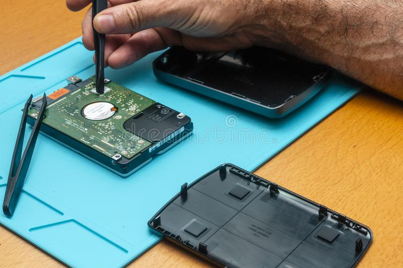 The process of repairing a hard drive by a repairman on a table royalty free stock image