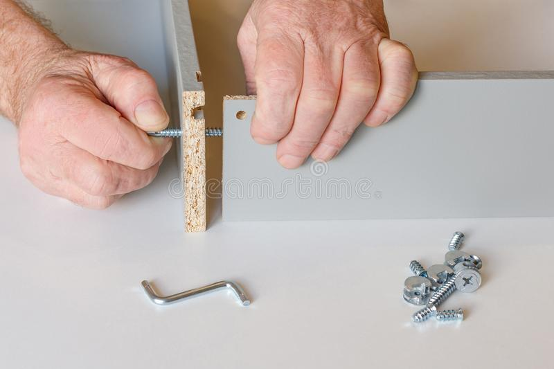The process of screed two walls of the kitchen box when assembling furniture. One of the screws is already tightened, the second royalty free stock photos