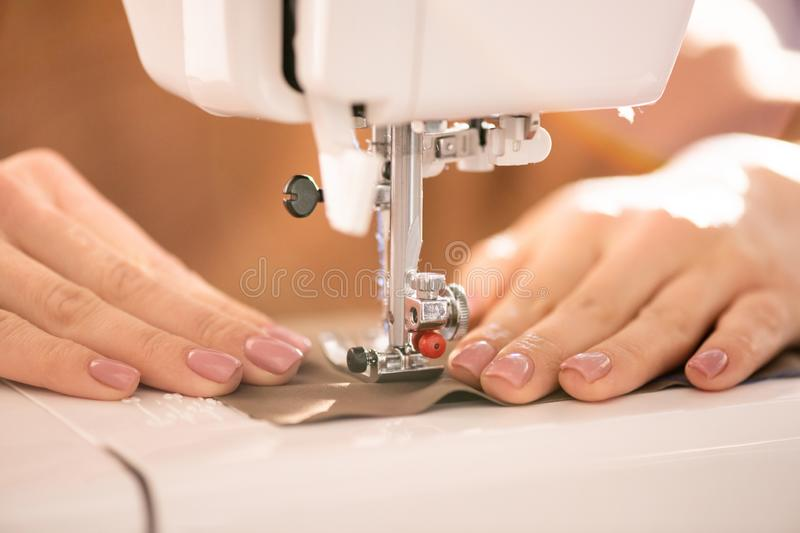 Process of sewing. Hands of seamstress holding a piece of textile under needle of electric sewing machine during work royalty free stock image