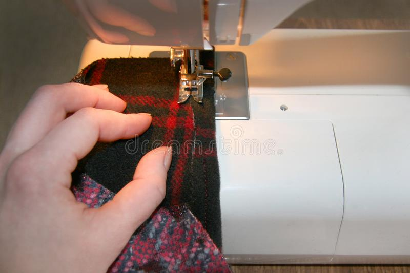 The process of sewing products, the girl performs the line on the machine, the hand holds a fabric stock images