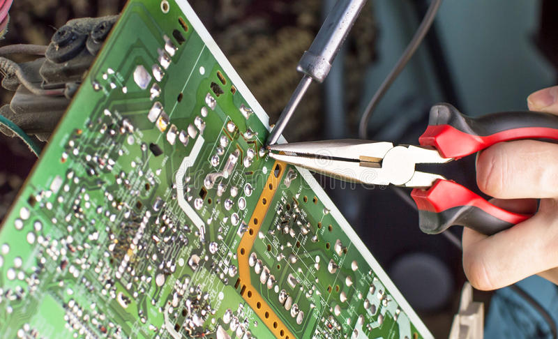 The process of soldering microcircuit tv. Using a soldering iron stock photo