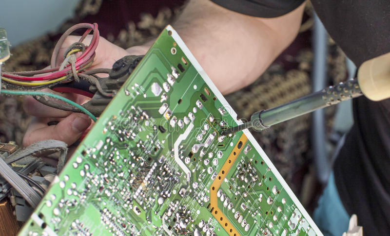 The process of soldering microcircuit TV. Using a soldering iron royalty free stock photography