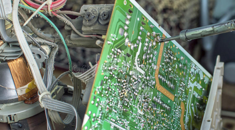 The process of soldering microcircuit TV. Using a soldering iron stock images