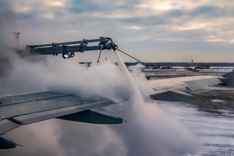 A process of spraying anti-icing white fluid the rear part of the wing of a plane at the airport in winter royalty free stock photography