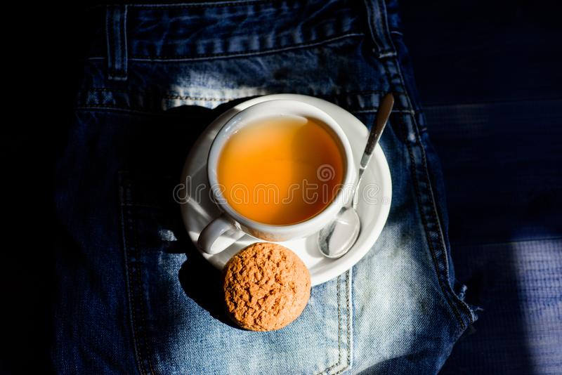 Process tea brewing ceramic mug. Inspiration and peaceful mood. Quick snack concept. Relaxing chamomile tea. Cup mug hot. Tea and oat cookie. Mug filled tea stock photo