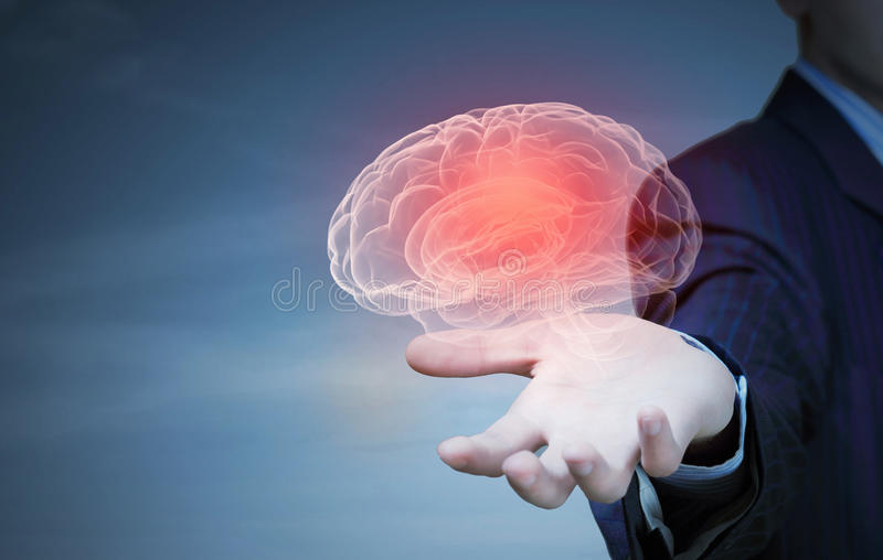 Process of thinking. Close up of businessman holding human brain with working gears stock image