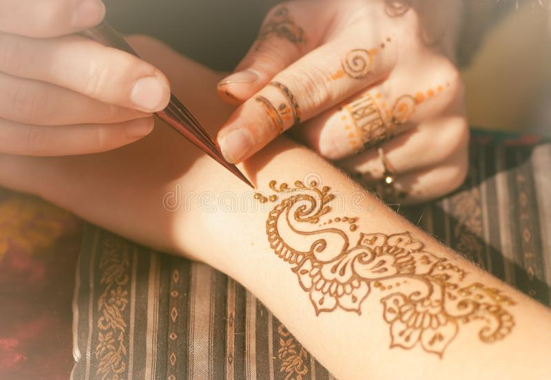 Process to draw mehendi. Master mehendi draws a henna on a woman`s hand royalty free stock images