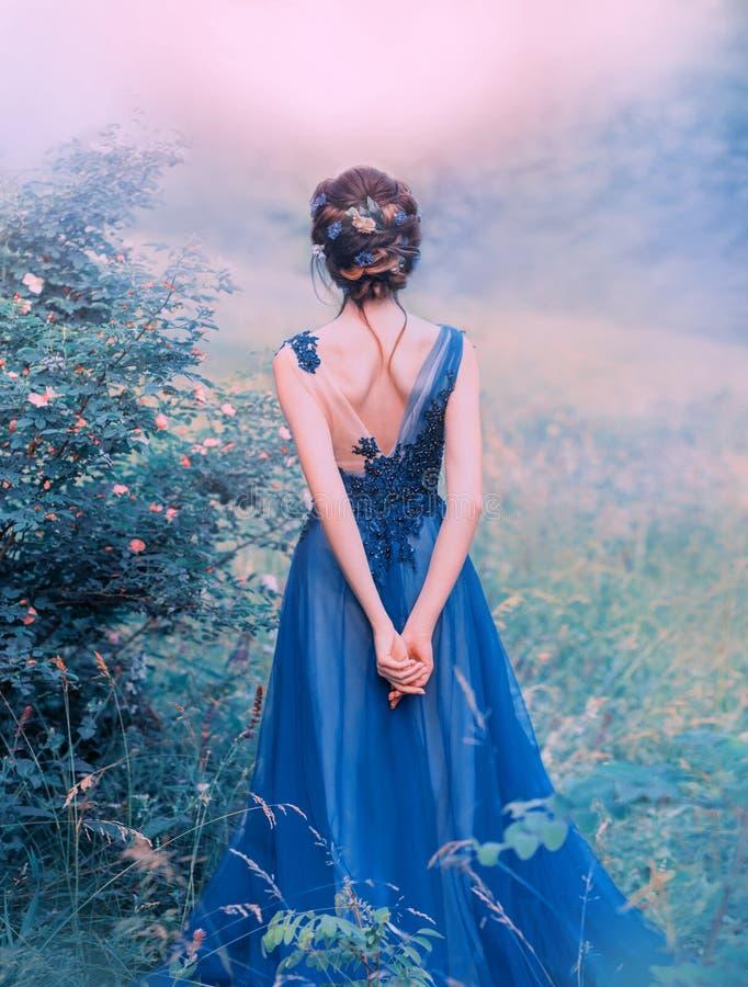 Processamento de fotos criativas com as flores frescas incomuns, uma menina doce da arte com cabelo voado preto, flores decoradas imagem de stock