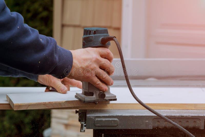 Processando o carpinteiro com o roteador eletrônico do mergulho de placas de madeira entregue o close-up do cortador imagem de stock royalty free