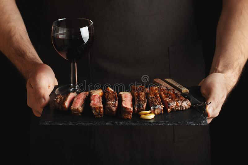 Man holding juicy grilled beef steak with spices and red wine glass on a stone cutting board on a black background royalty free stock photo