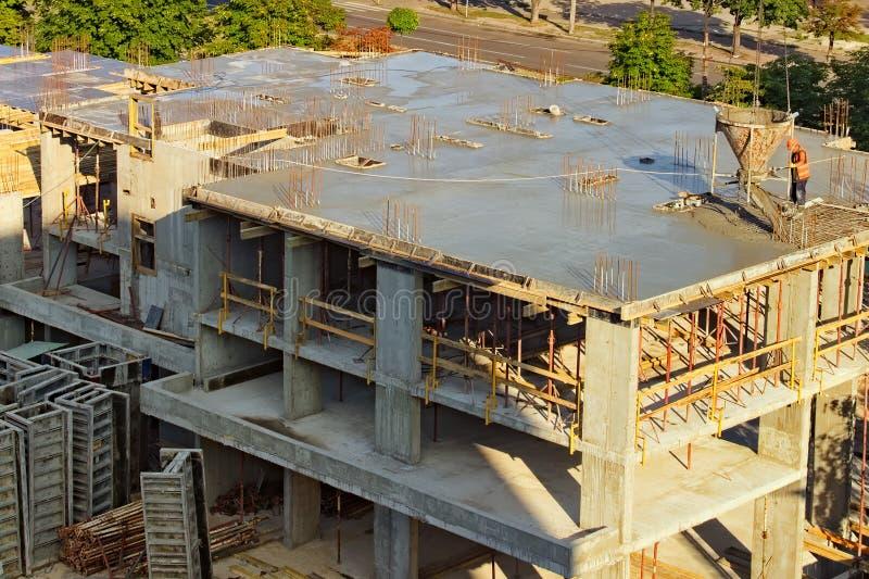processen av att bygga m?ng--v?ning en bostads- byggnad Processen av att hälla det nya golvet av byggnaden med betong arkivbilder