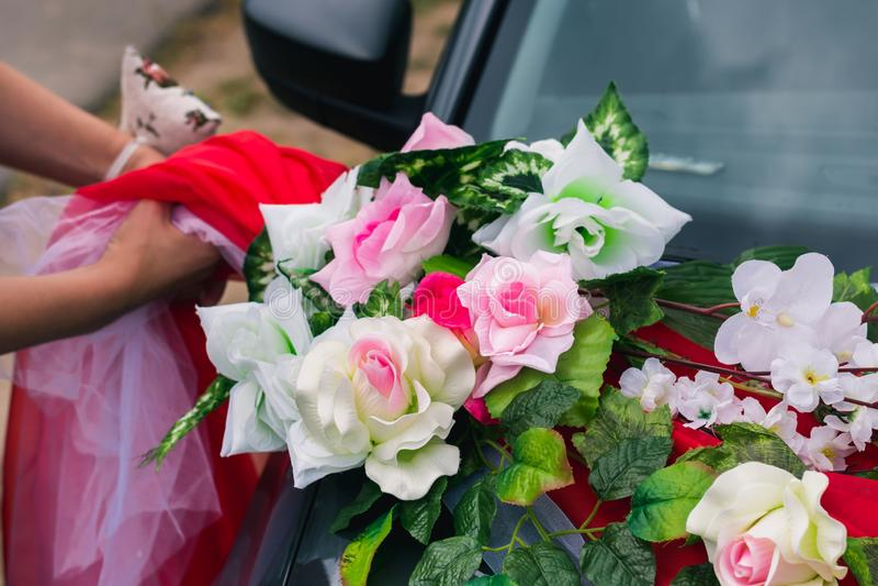 Processen av att dekorera en gifta sig bil med konstgjorda blommor och gardin arkivfoton