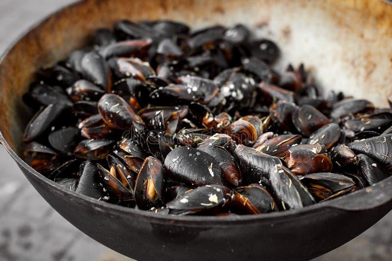 Processen av att förbereda musslor i en stor kastrull Gatamat med skaldjur royaltyfri fotografi