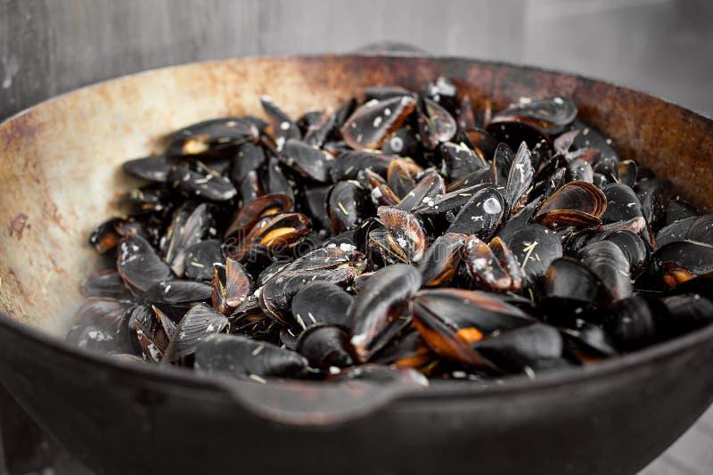 Processen av att förbereda musslor i en stor kastrull Gatamat med skaldjur royaltyfria bilder