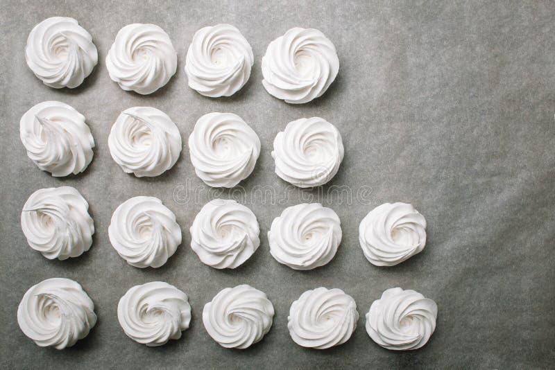 Processen av att göra marshmallowen Stäng sig upp händer av kocken med konfektpåsekräm till pergamentpapper på bakelse shoppar arkivfoton