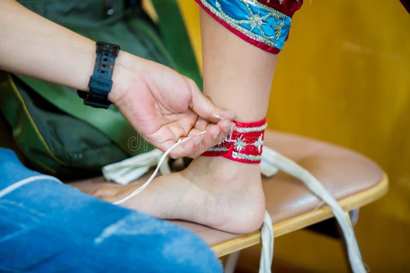Processen av att klä den thailändska pantomimen för skådespelarna med handen som syr som reparerar arkivbild