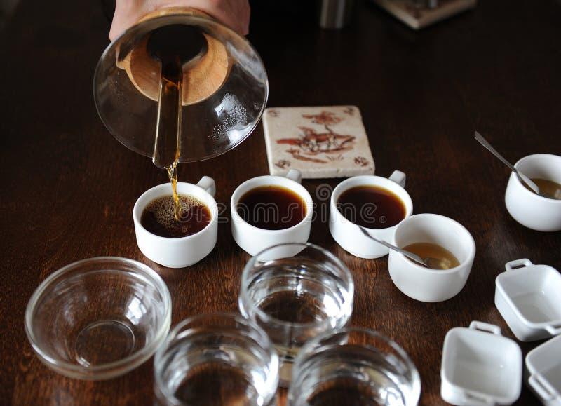 Processen av att kupa för kaffe Kaffe hälls in i avsmakningkoppar royaltyfria foton