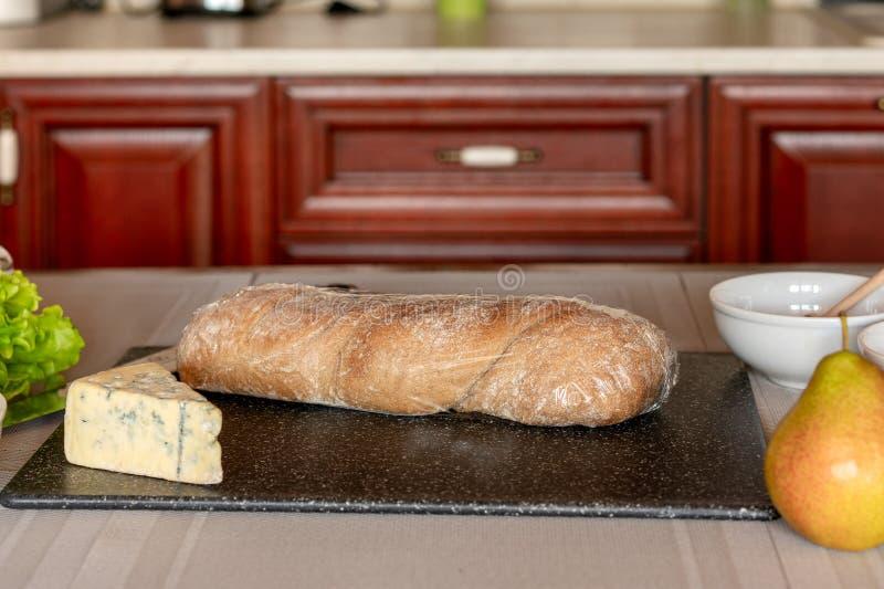 Processen av att laga mat bruschetta med päronet, honung, valnöten, ost, grön sallad och olivolja royaltyfria foton
