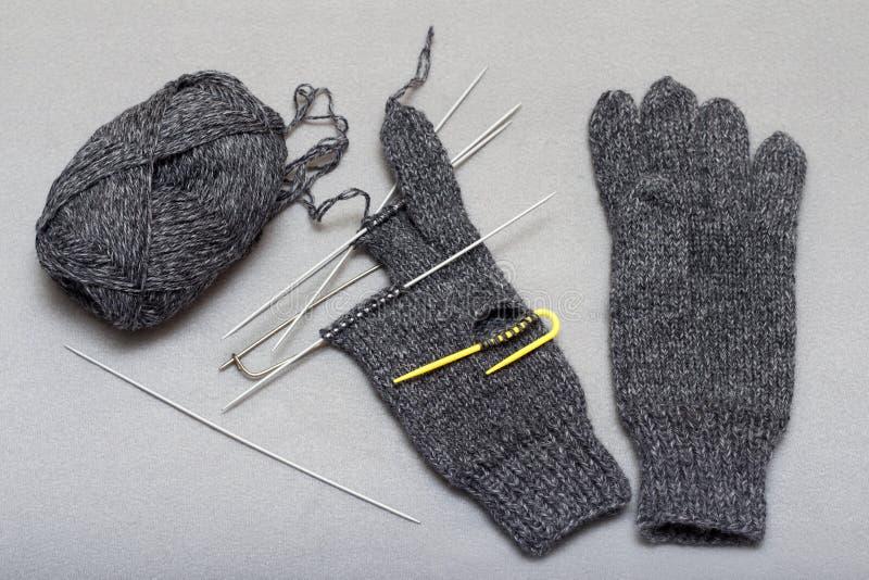 Processen av att sticka woolen handskar på stickor arkivbilder