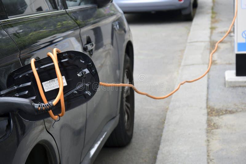 Processen av att uppladdning en elbil arkivbild