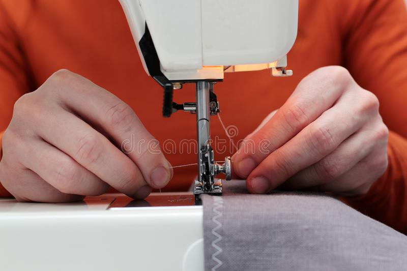 Processes of sewing flax on the sewing machine sew women`s hands sewing machine Linum. sewing machine and female fingers out of stock image