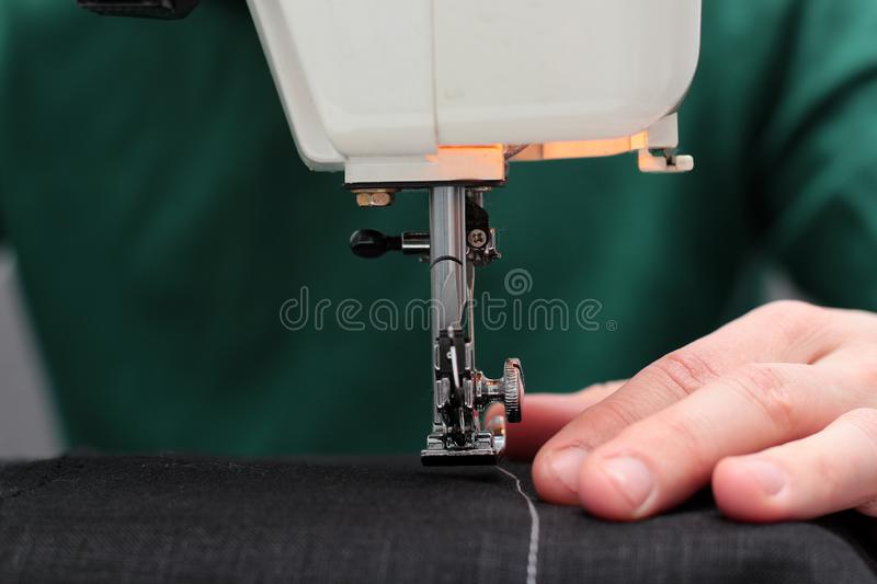 Processes of sewing Linum on the sewing machine sew women`s hands sewing machine Linum. sewing machine and female fingers out of stock photo