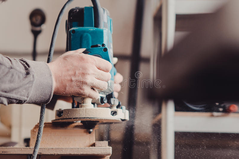 Processing of a furniture part by a machine for polishing a tree royalty free stock photo