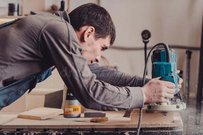 Processing of a furniture part by a machine for polishing a tree royalty free stock photography