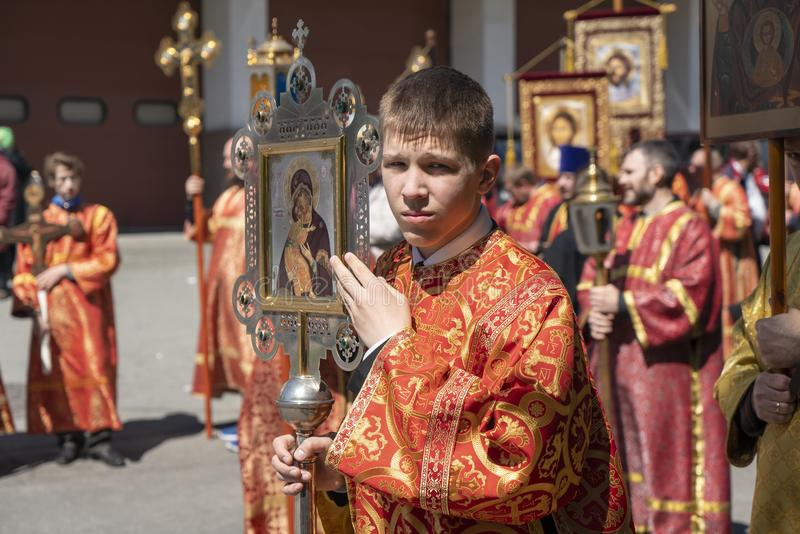 Procession in honor of the celebration of Russian Literature, a Young priest in Church vestments holding a flag with an Orthodox i. Chelyabinsk, Russian stock photo